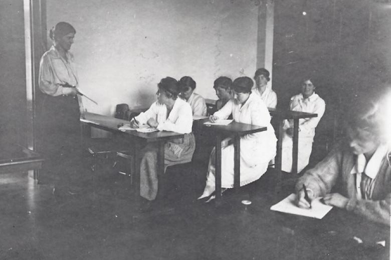 Eileen Power teaching in a classroom at Girton College taken by Bassano Ltd, 1919 (archive reference: GCPH 7/1/7)